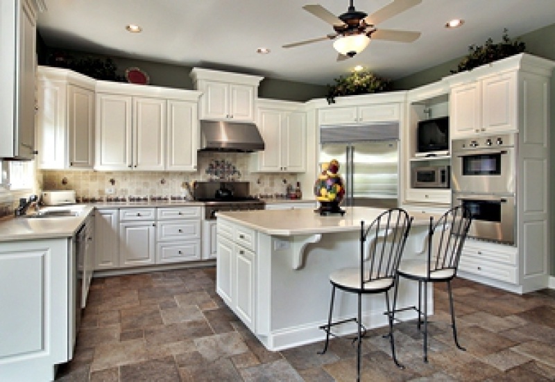 Renovaated kitchen with white cabinets, central island, and stainless steel appliances