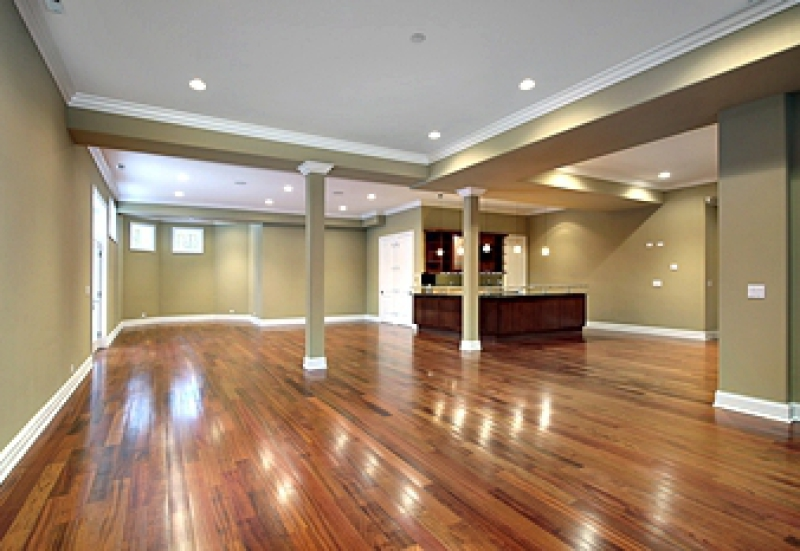 Remodeled basement with a beautiful wood floor and recessed lighting