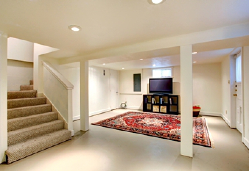 Tasteful basement renovation with an area rug and entertainment center