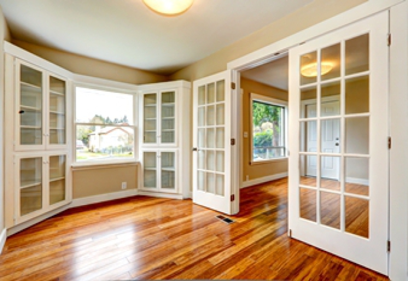 Interior doors with glass panes contrasted against a hardwood floor