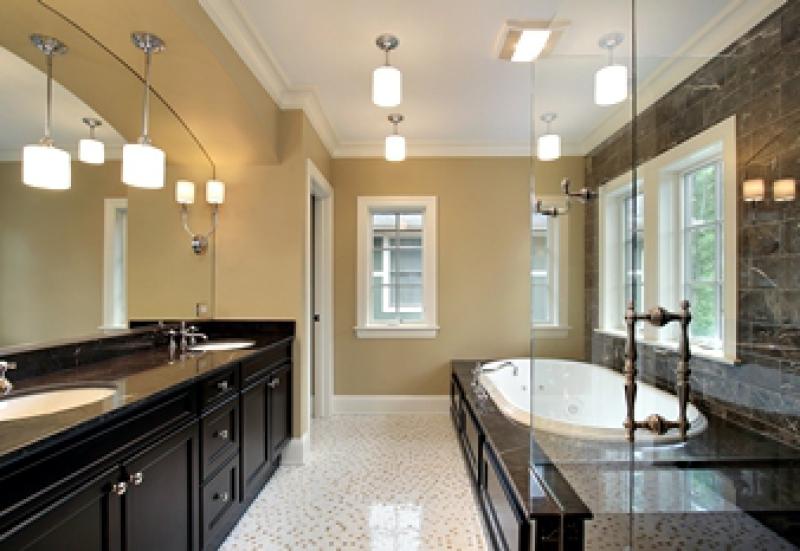 Bathroom with platform bathtub and dark vanity with two sinks