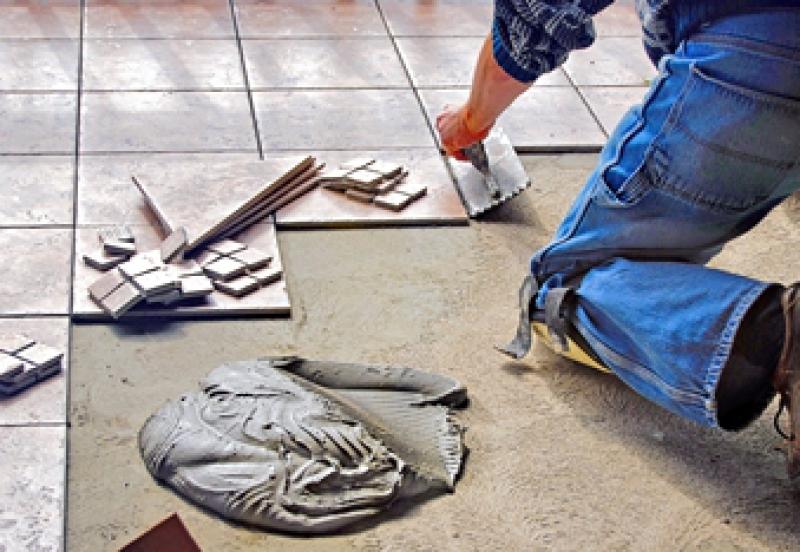 Worker installing porcelain floor tile